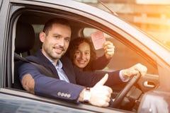 Jeunes couples d'homme d'affaires dans leur voiture toute neuve photos stock