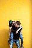 Jeunes couples d'Inlove posant dans le style de mode sur le mur jaune Photo stock