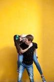 Jeunes couples d'Inlove posant dans le style de mode sur le mur jaune Photos libres de droits