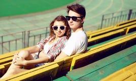 Jeunes couples dans étreindre se reposant d'amour, de type et de fille sur le stade de ville Photographie stock