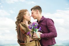 Jeunes couples dans des étreintes d'amour doucement contre le ciel bleu et les nuages blancs Photographie stock