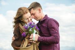 Jeunes couples dans des étreintes d'amour doucement contre le ciel bleu et les nuages blancs Images libres de droits