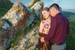 Jeunes couples dans des étreintes d'amour doucement contre le ciel bleu et les nuages blancs Images stock
