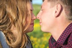 Jeunes couples dans des étreintes d'amour doucement contre le ciel bleu et les nuages blancs Photos libres de droits