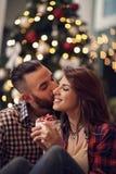 Jeunes couples dans des baisers d'amour au réveillon de Noël Image stock