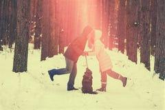 Jeunes couples dans des baisers d'amour extérieurs en hiver au coucher du soleil Photographie stock libre de droits