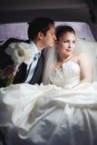 Jeunes couples dans des baisers de limousine Image stock