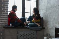 Jeunes couples dans des chandails tricotés chauds regardant le whi de fenêtre Images libres de droits