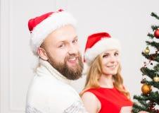 Jeunes couples dans des chapeaux de Noël à côté d'un arbre de Noël Photographie stock libre de droits