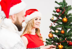 Jeunes couples dans des chapeaux de Noël à côté d'un arbre de Noël Images libres de droits