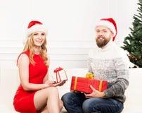 Jeunes couples dans des chapeaux de Noël tenant des présents Photographie stock