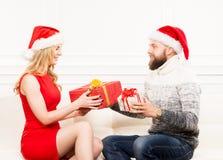 Jeunes couples dans des chapeaux de Noël tenant des présents Image libre de droits
