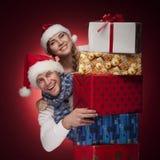 Jeunes couples dans des chapeaux de Santa avec des présents d'isolement Photographie stock libre de droits