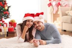 Jeunes couples dans des chapeaux de Santa Claus Image stock