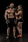 Jeunes couples dans des gants de vêtements de sport et de boxe se tenant ensemble et souriant à l'appareil-photo Photographie stock