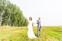 Jeunes couples dans des jeunes mariés d'amour posant dans un domaine avec l'herbe jaune dans leur jour du mariage pendant l'été Photos libres de droits