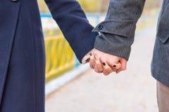 Jeunes couples dans des mains de fixation d'amour Photographie stock libre de droits