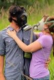 Jeunes couples dans des masques de gaz s'usants d'amour Photos stock