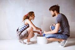 Jeunes couples dans des murs de peinture d'amour dans leur nouvelle maison Photographie stock libre de droits