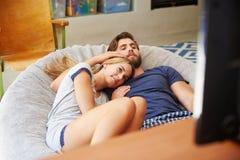 Jeunes couples dans des pyjamas regardant la télévision ensemble Photo stock