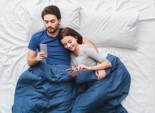 Jeunes couples dans des smartphones de lecture rapide de concept de matin de vue supérieure de lit Images stock