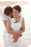 Jeunes couples dans des vêtements blancs en mer Image libre de droits
