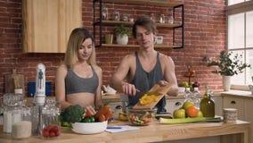 Jeunes couples dans des vêtements de sports se tenant derrière la table de cuisine préparant sur la salade fraîche de lunc avec d clips vidéos