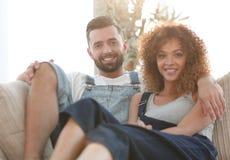 Jeunes couples dans des vêtements de travail se reposant sur le divan Image stock