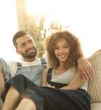 Jeunes couples dans des vêtements de travail se reposant sur le divan Photographie stock