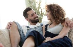 Jeunes couples dans des vêtements de travail se reposant sur le divan Photo libre de droits