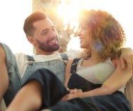 Jeunes couples dans des vêtements de travail se reposant sur le divan Photos libres de droits
