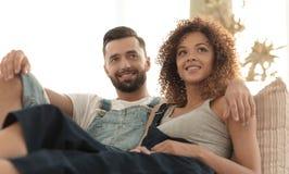 Jeunes couples dans des vêtements de travail se reposant sur le divan Images stock