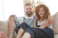 Jeunes couples dans des vêtements de travail se reposant sur le divan Image libre de droits