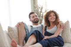 Jeunes couples dans des vêtements de travail se reposant sur le divan Photos stock