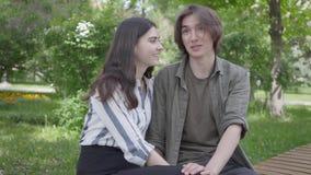 Jeunes couples dans des vêtements sport se reposant au banc parlant et tenant des mains Fille heureuse et gar?on passant le temps banque de vidéos