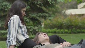 Jeunes couples dans des v?tements sport passant le temps ensemble dehors, ayant la date La fille s'asseyant sur l'herbe, elle banque de vidéos