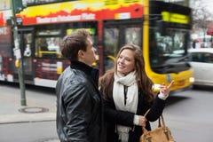 Jeunes couples dans des vestes communiquant la rue Image stock