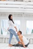 Jeunes couples dans l'amour à la maison, homme s'asseyant sur le plancher Photos libres de droits