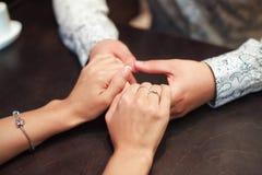 Jeunes couples dans l'amour étreignant des mains à travers la table image libre de droits