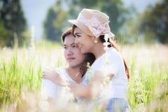 Jeunes couples dans l'amour étreignant et se reposant dans le pré Photos stock