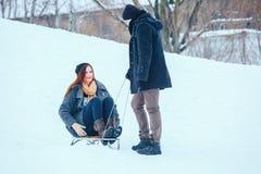 Jeunes couples dans l'amour appréciant des vacances d'hiver et ayant l'amusement un jour neigeux d'hiver Photos stock
