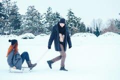Jeunes couples dans l'amour appréciant des vacances d'hiver et ayant l'amusement un jour neigeux d'hiver Photo stock