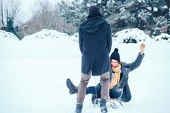 Jeunes couples dans l'amour appréciant des vacances d'hiver et ayant l'amusement un jour neigeux d'hiver Photographie stock