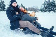 Jeunes couples dans l'amour appréciant des vacances d'hiver et ayant l'amusement un jour neigeux d'hiver Images libres de droits