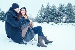 Jeunes couples dans l'amour appréciant des vacances d'hiver et ayant l'amusement un jour neigeux d'hiver Image libre de droits