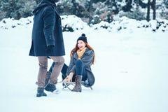 Jeunes couples dans l'amour appréciant des vacances d'hiver et ayant l'amusement un jour neigeux d'hiver Photographie stock libre de droits
