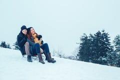 Jeunes couples dans l'amour appréciant des vacances d'hiver et ayant l'amusement un jour neigeux d'hiver Images stock