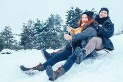 Jeunes couples dans l'amour appréciant des vacances d'hiver et ayant l'amusement un jour neigeux d'hiver Photos libres de droits