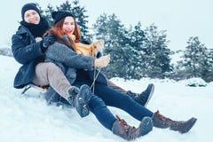 Jeunes couples dans l'amour appréciant des vacances d'hiver et ayant l'amusement un jour neigeux d'hiver Photo libre de droits
