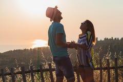 Jeunes couples dans l'amour appréciant le coucher du soleil Photos stock